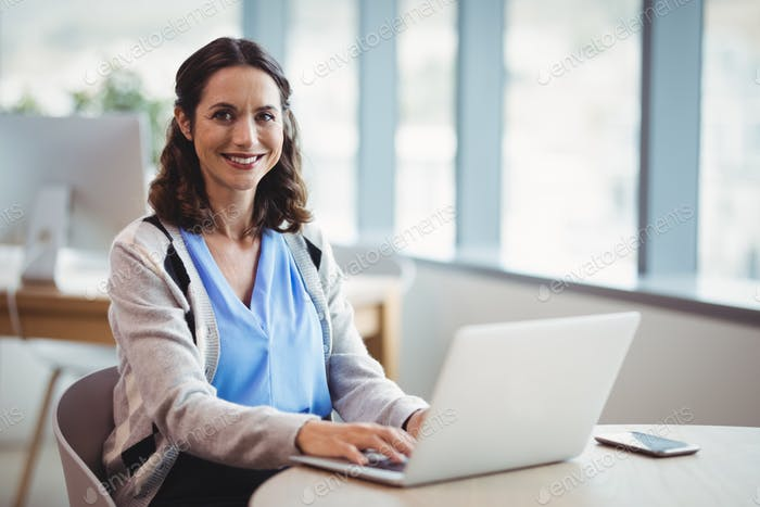 Portrait smiling executive using laptop at desk