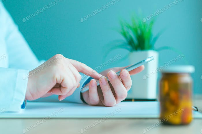 General practitioner using smartphone in office