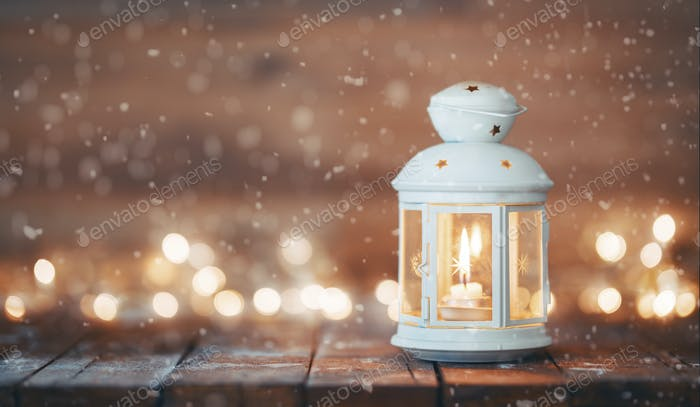 Lantern with a candle on wooden background