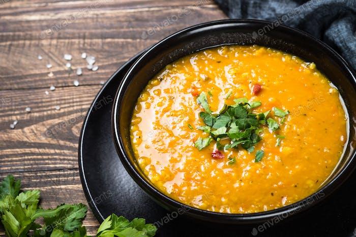 Red lentil soup in black bowl