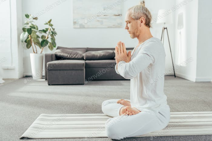 side view of man meditating in lotus position with namaste gesture at home