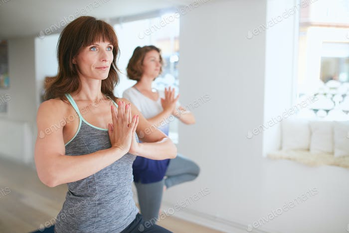 Two women practice yoga together