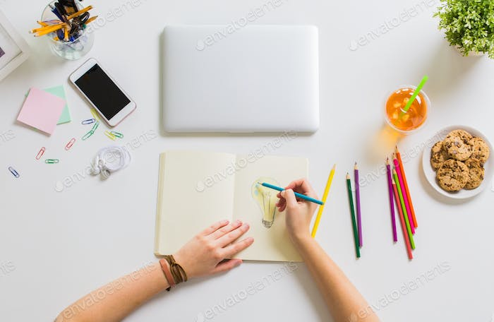 woman hands drawing in notebook at home office