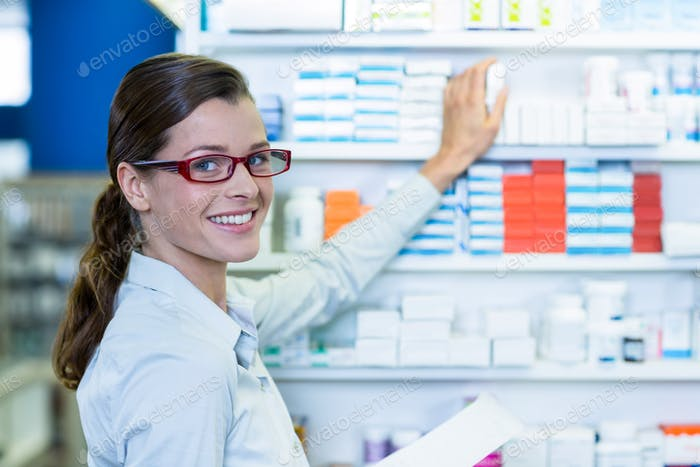 Pharmacist holding prescription while checking medicine in pharmacy