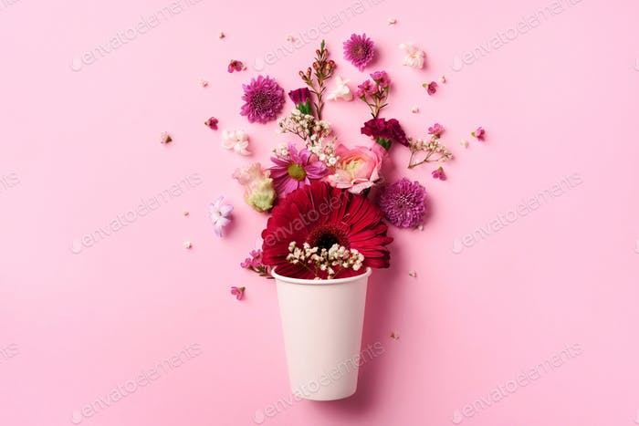Creative layout made of white paper cup with pink flowers. Flat lay, top view. Banner with copy
