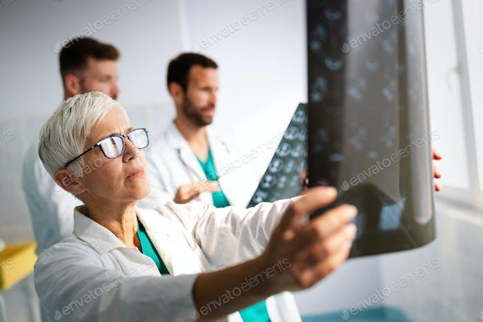 Gruppe von Arzt Blick auf ct Scan im Krankenhaus, um Diagnose zu stellen