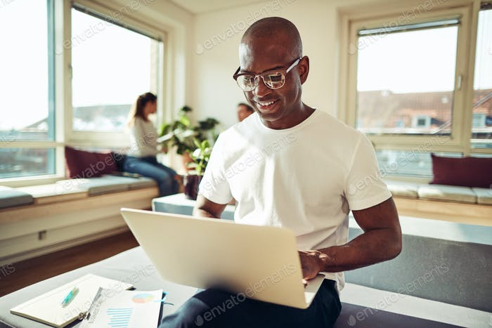 Smiling African businessman working online with colleagues in the background