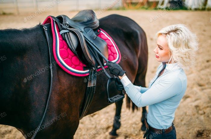 Female rider preparing a horse saddle,
