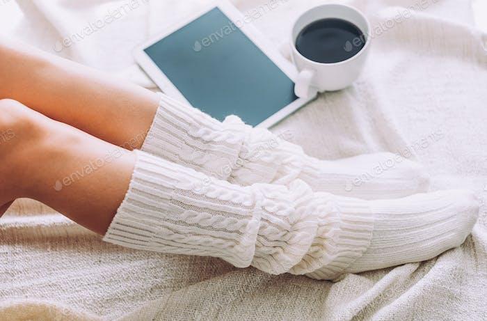 Nahaufnahme der Beine der Frau auf dem Bett. Junge Frau genießt ihren Aufenthalt zu Hause.