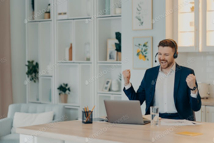Excited successful businessman enjoying triumph with clenched fists