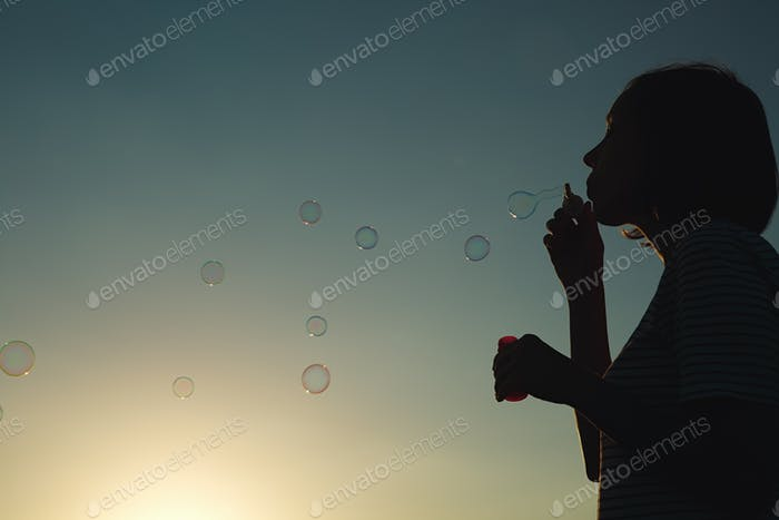 Girl inflates soap bubbles.