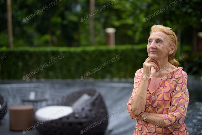 Beautiful senior tourist woman with blond hair relaxing around t