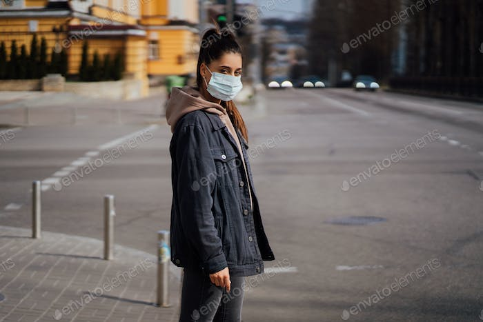 Close up of young woman with surgical mask on face