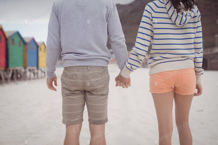 Couple holding hands while standing at beach