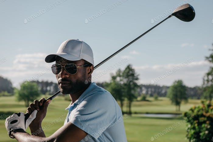Portrait of Focused African American Man Playing Golf at Golf Course