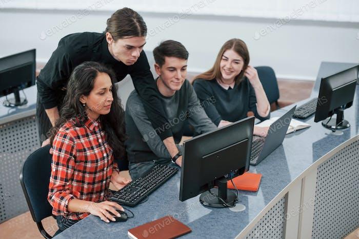 Nach einem Plan. Gruppe junger Leute in Freizeitkleidung, die im modernen Büro arbeiten