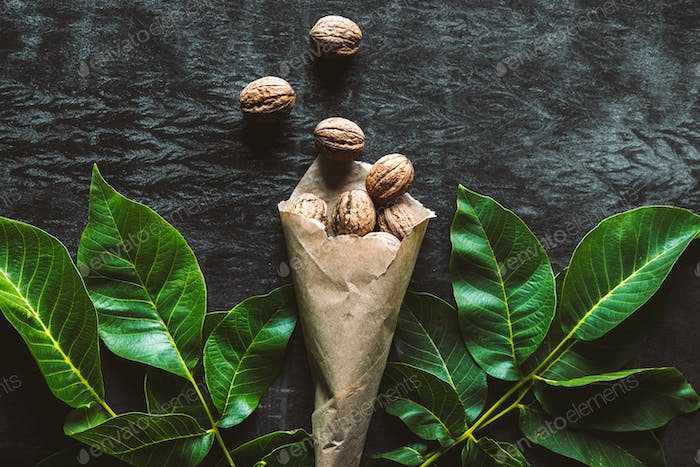 Walnuts on a old rustic table. Walnuts in a paper bag. Walnuts in paper walnut leaves. Vintage style