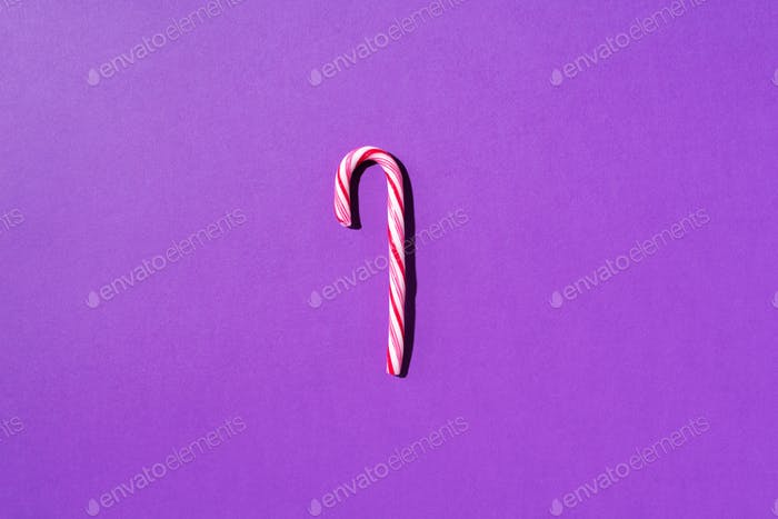 Christmas candy cane on violet background with copy space. Top view. Greeting card on Christmas and
