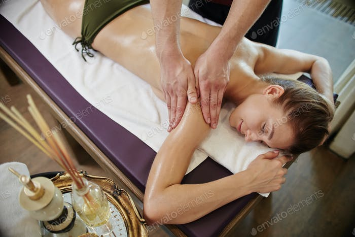 Male Masseuse Massaging Young Woman in SPA