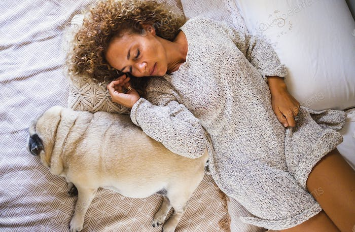 Young adult woman sleeping on bed beside her pet dog at home in bed. Woman with dog