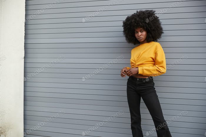 Hip young black woman standing in the street against grey security shutters, looking to camera
