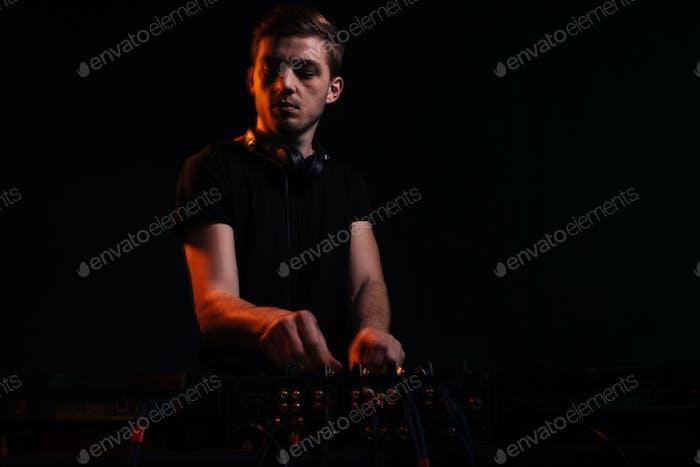 DJ играет музыку на микшере на красочном туманном фоне