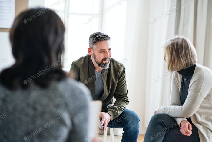 Man and women sitting in a circle during group therapy, talking.