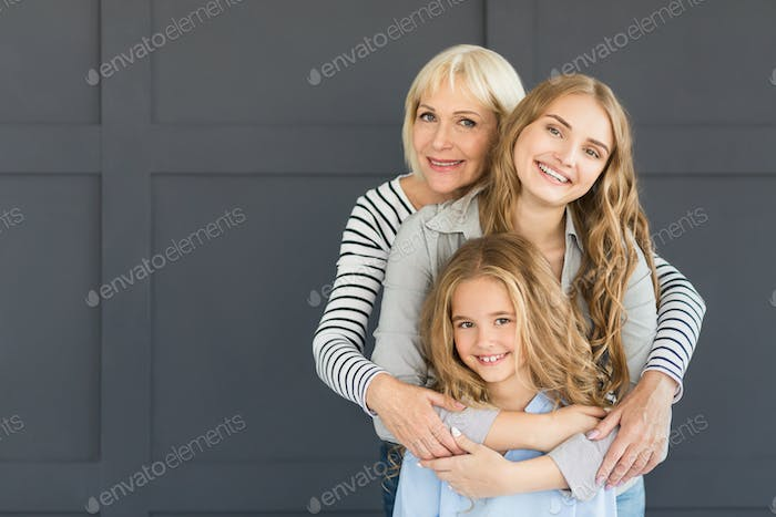 Women hugging, looking at camera and smiling