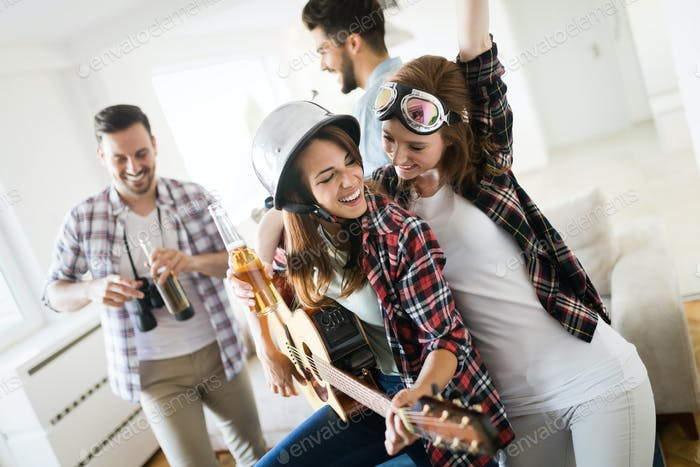 Cheerful friends having party together and playing instruments