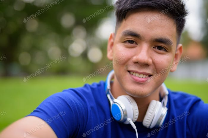 Young handsome Asian man relaxing at the park wearing headphones