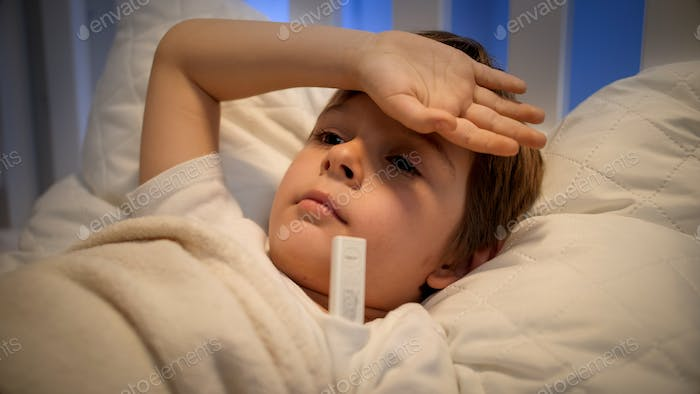 Little sick boy feeling unwell lying in bed and measuring temperature. Concept of children illness