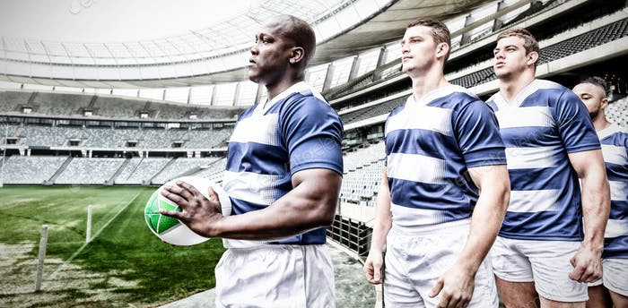 Digital composite image of team of rugby players standing in a row in sports stadium