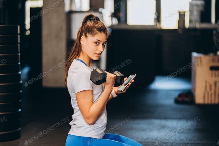 Schlanke athletische Mädchen führt körperliche Übungen mit Hanteln