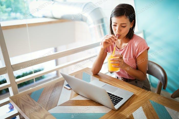 Porträt einer fröhlichen schönen Frau arbeitet, studiert auf einem Laptop