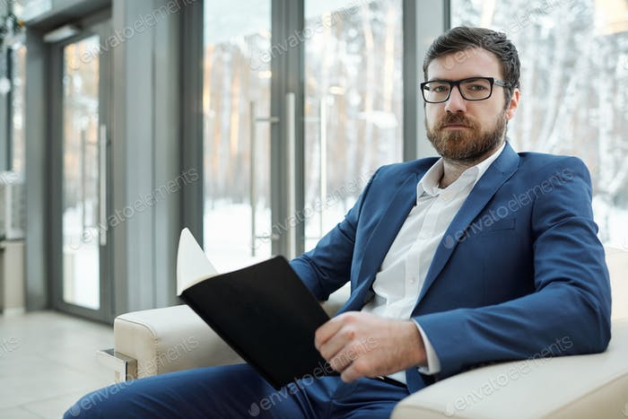 Serious young businessman in elegant suit, white shirt and eyeglasses