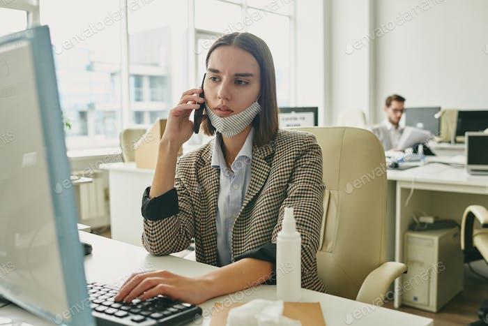 Serious businesswoman pushing keyboard key while looking at computer screen
