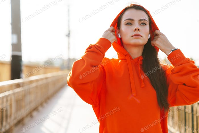 Fitness woman outdoors listening music with earphones.