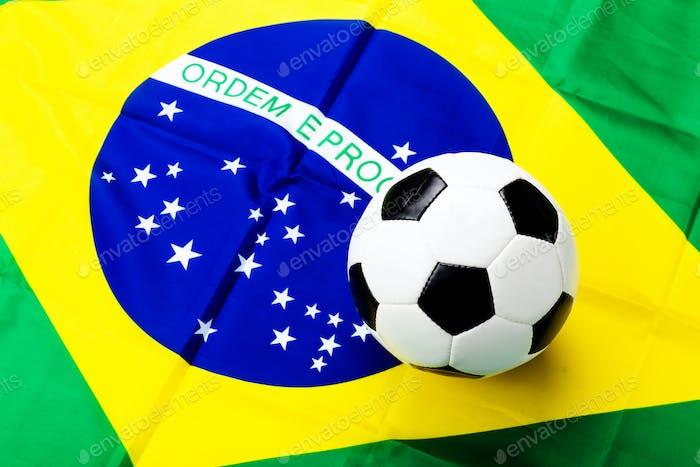 Waved Brazilian flag and football