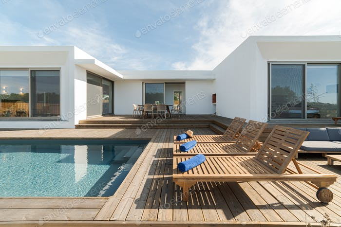 Lounge chairs in modern villa pool