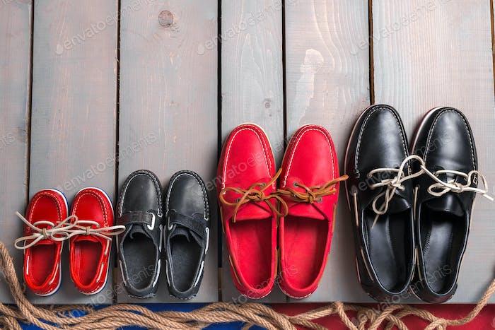 Sapatos de barco família em fundo de madeira.