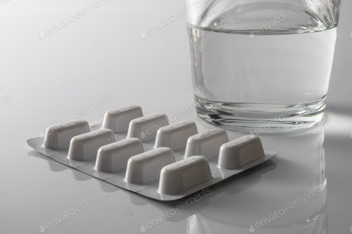 Pills Blister along with a water glass, conceptual image