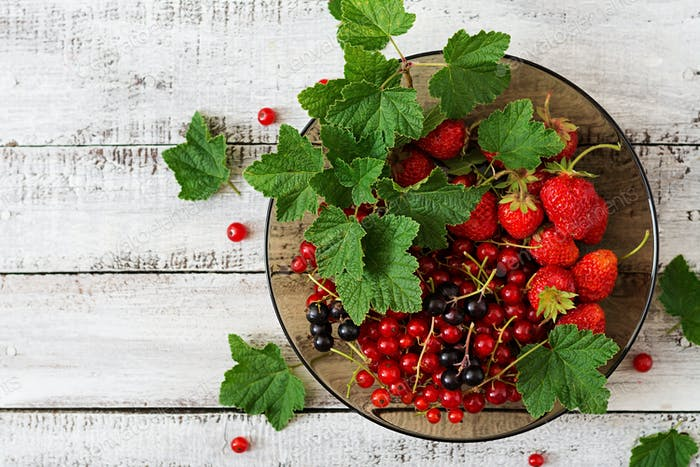 Plate with fresh berries (strawberries and currants) on wooden background. Top view