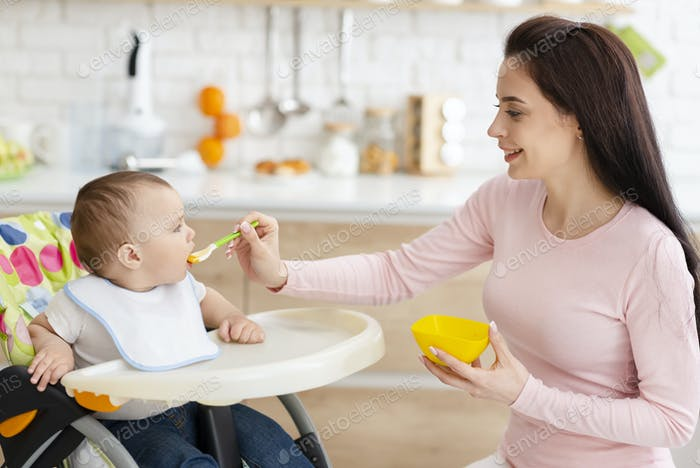Mutter füttert ihr Baby, Kleinkind sitzt im Hochstuhl in der Küche
