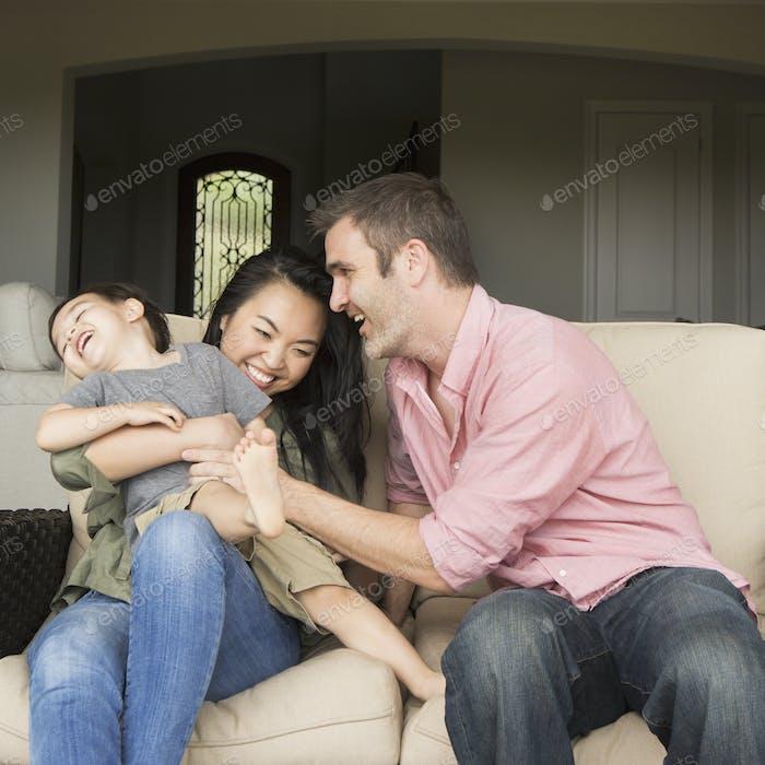 Eine Familie, ein Mann und eine Frau, die nebeneinander auf einem Sofa sitzen und mit ihrem kleinen Sohn spielen.