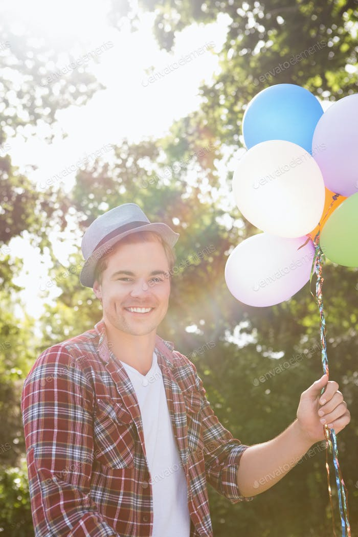 Handsome hipster holding balloons on a sunny day