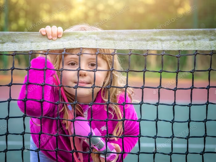 Girl looking through the tennis net