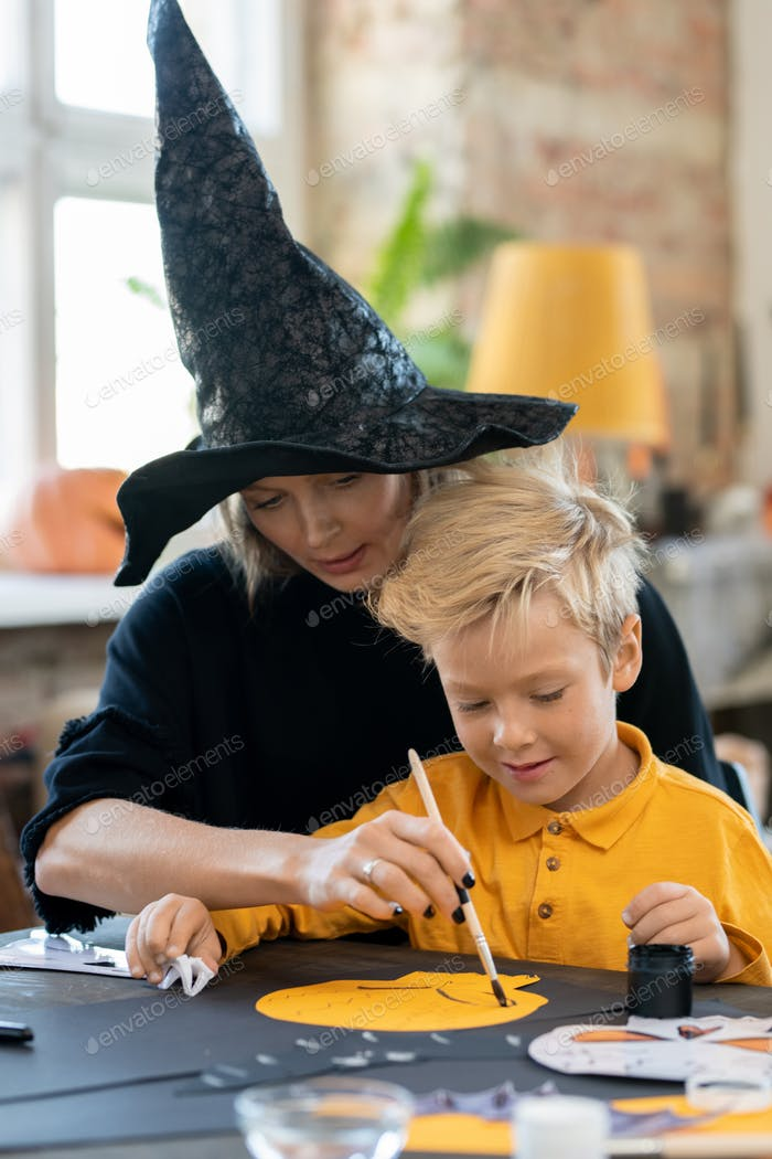 Assisting boy to paint skeleton
