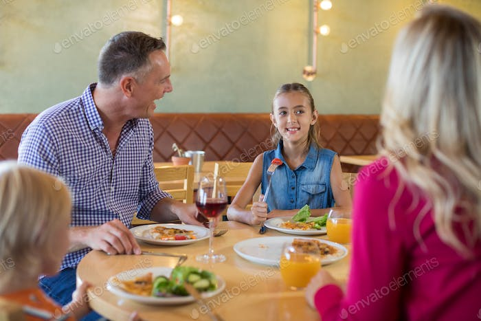 Happy family talking while having food