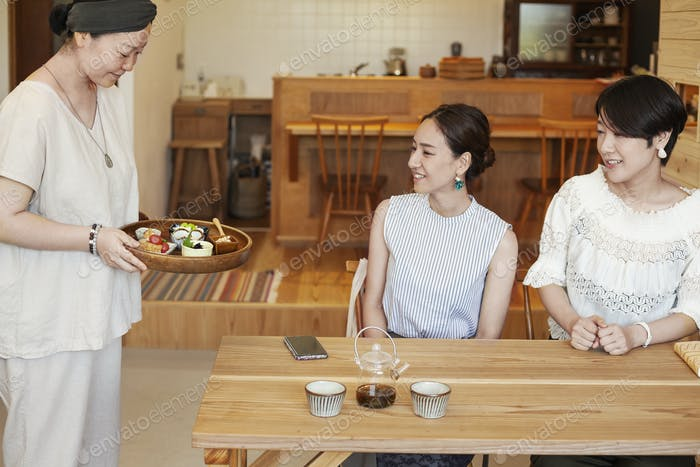 Japanese woman serving two female customers in a vegetarian cafe.