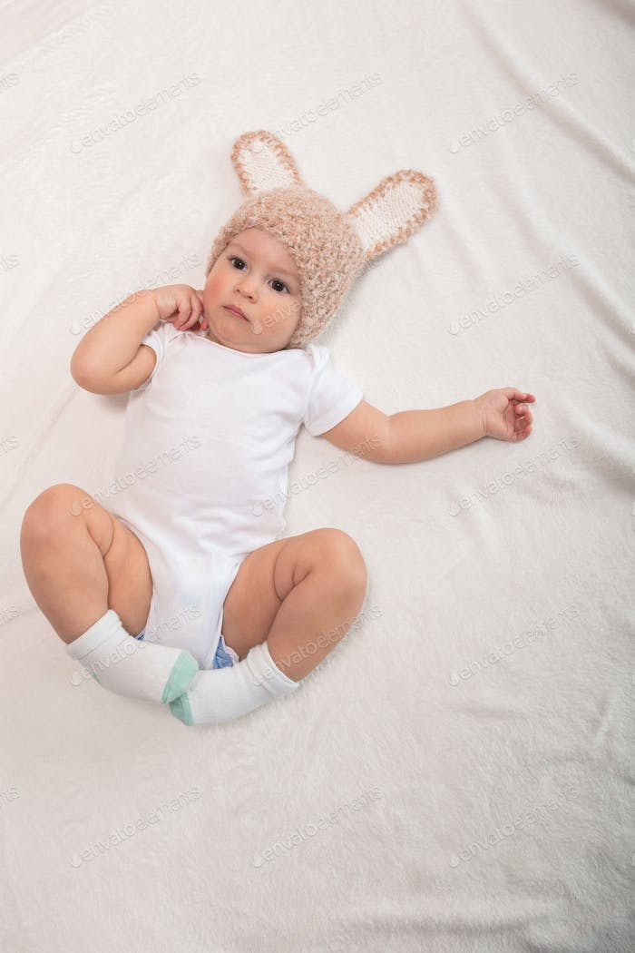Cute baby boy in funny hat with ears lying on bed
